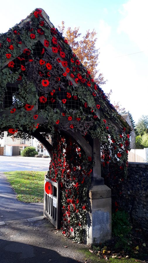 Knitted poppies adorning the Lych Gate on Remembrance Sunday 2018 at St Vigor's Parish Church, Fulbourn, Cambridgeshire