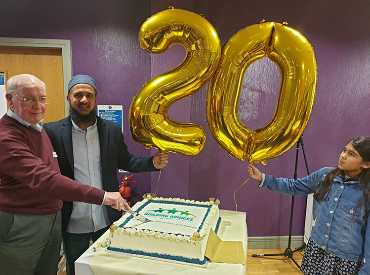 20 years of influential interfaith work -balloons and cake cutting